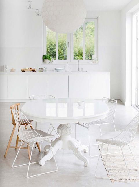 All white dining room with mismatched chairs
