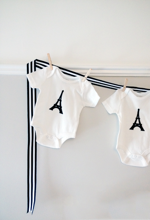 Baby shower decor: adorable onesies pinned to grossgain ribbon