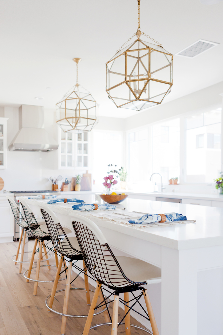 White kitchen with brass pendants