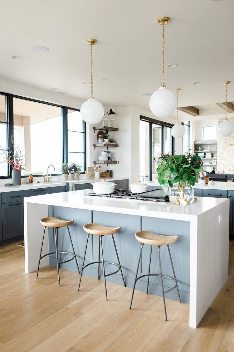 25Modern+kitchen+with+open+shelves,+natural+wood+barstools,+blue+cabinets+with+white+waterfall+edged+countertops