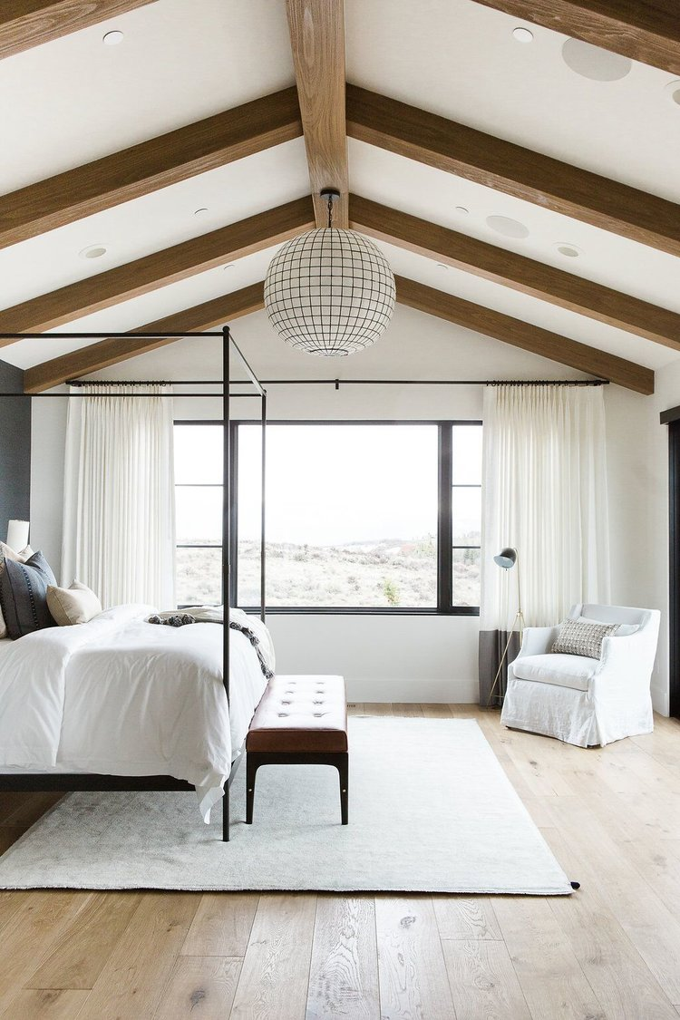 26Master+bedroom+in+blue+grasscloth+wallpaper,+statement+chandelier,+and+leather+bench