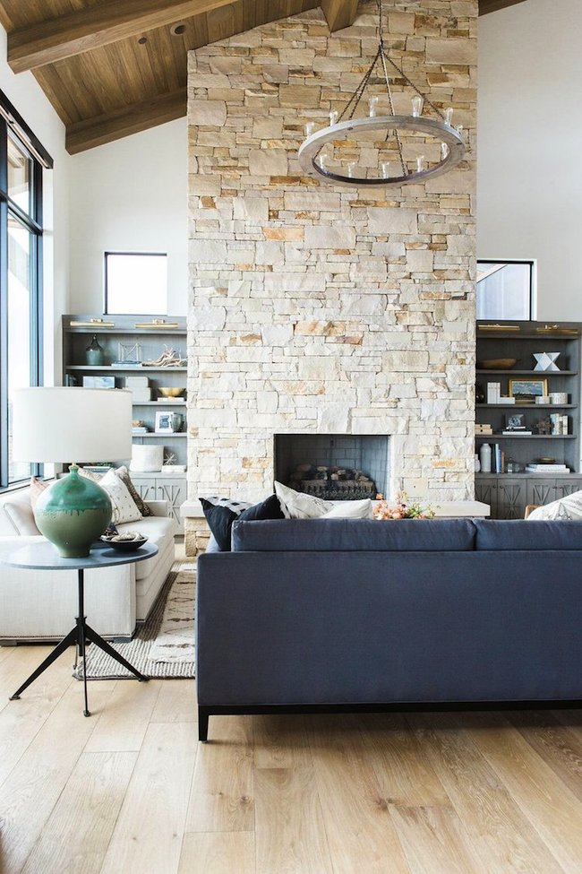 4Great+room+with+dramatic+stone+fireplace,+layered+rugs,+and+neutral+color+scheme